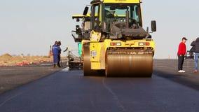Rodillos de camino que nivelan el pavimento fresco del asfalto almacen de metraje de vídeo