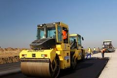 Rodillos de camino que nivelan el pavimento fresco del asfalto en una pista como parte del plan de expansión del aeropuerto inter Imagen de archivo