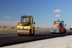 Rodillos de camino que nivelan el pavimento fresco del asfalto en una pista como parte del plan de expansión del aeropuerto inter Fotos de archivo