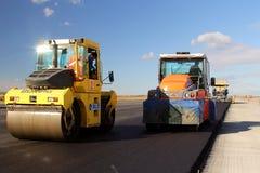 Rodillos de camino que nivelan el pavimento fresco del asfalto en una pista como parte del plan de expansión del aeropuerto inter Foto de archivo libre de regalías