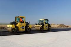 Rodillos de camino que nivelan el pavimento fresco del asfalto en una pista como parte del plan de expansión del aeropuerto inter Fotos de archivo libres de regalías