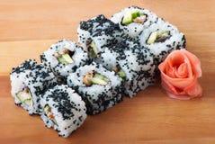 Rodillos de sushi de California en la placa de madera Imagenes de archivo