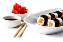 Rodillos de sushi deliciosos en la placa blanca con los palillos y wasabi Foto de archivo libre de regalías