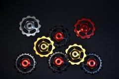 Rodillos del color, negro, rojo, oro, engranajes de plata para el derailleur posterior de la bici colocado caótico en fondo negro fotos de archivo