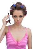 Rodillos del pelo de la mujer que llevan seria con el teléfono Imágenes de archivo libres de regalías