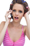Rodillos del pelo del modelo que llevan joven atractivo con el teléfono Fotos de archivo libres de regalías