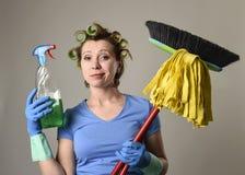 Rodillos estereotipados del pelo del ama de casa y guantes que se lavan que sostienen la escoba de la fregona y la botella deterg Fotografía de archivo