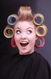 Rodillos rubios alegres divertidos de los bigudíes de pelo de la muchacha del peluquero en salón Foto de archivo