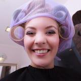Rodillos rubios divertidos alegres de los bigudíes de pelo de la muchacha por el haidresser en salón de belleza Imagenes de archivo