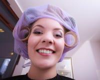 Rodillos rubios divertidos alegres de los bigudíes de pelo de la muchacha por el haidresser en salón de belleza Imagen de archivo