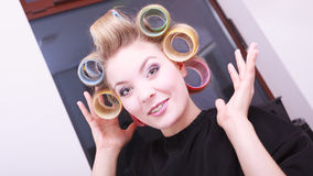 Rodillos rubios felices de los bigudíes de pelo de la muchacha del peluquero en salón de belleza Fotos de archivo libres de regalías