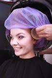 Rodillos rubios felices de los bigudíes de pelo de la muchacha por el haidresser en salón de belleza Imagen de archivo libre de regalías