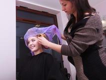 Rodillos rubios felices de los bigudíes de pelo de la muchacha por el haidresser en salón de belleza Imágenes de archivo libres de regalías
