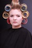 Rodillos rubios infelices de los bigudíes de pelo de la muchacha. salón. Fotos de archivo libres de regalías