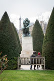 Rodin. Couple sitting on a bench admiring le penseur sculpture of rodin, with the tip of the eiffel tower on the background. image framed by trees. paris, france Royalty Free Stock Photos
