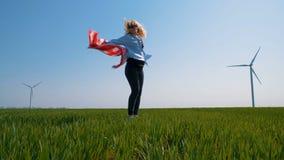 Rodowity Amerykanin dziewczyna z flaga blisko gigantycznego wiatraczka w polu w zwolnionym tempie zbiory