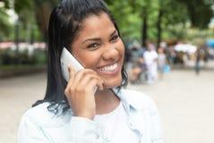 Rodowity Amerykanin kobieta śmia się przy telefonem w parku Obrazy Stock