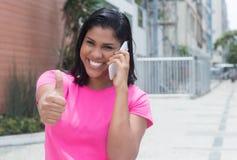 Rodowity Amerykanin kobieta przy telefonem pokazuje kciuk w mieście Obraz Stock