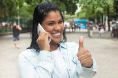 Rodowity Amerykanin kobieta przy telefonem w parkowym pokazuje kciuku Obraz Royalty Free
