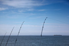 Rods. Four rods with a big ship in the blue horizon Stock Photos