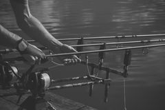 Rods, reels, lines and male hands on water background, fishing stock photography