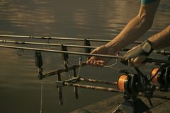 Rods, reels, lines and male hands on water background, fishing royalty free stock images