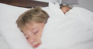 Rodzeństwa śpi na łóżku w sypialni przy wygodnym domem 4k zbiory wideo