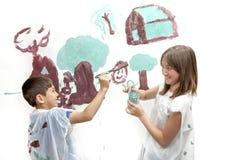 Rodzeństwa bawić się podczas gdy malujący Zdjęcie Royalty Free