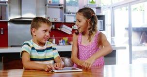 Rodzeństwa daje wysokości pięć each inny podczas gdy używać cyfrową pastylkę w kuchni zbiory wideo