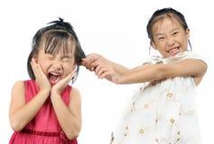 Rodzeństwa dokucza, azjatykcia mała dziewczynka ciągnie jej siostry włosy obraz stock