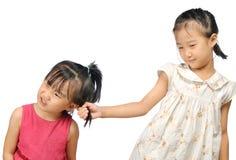 Rodzeństwa dokucza, azjatykcia mała dziewczynka ciągnie jej siostry włosy obraz royalty free
