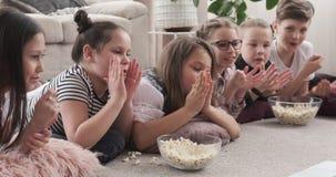 Rodzeństwa je popkorn i klascze ręki podczas gdy oglądający film zbiory wideo