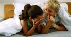 Rodzeństwa oddziała wzajemnie z each inny na łóżku w sypialni zbiory