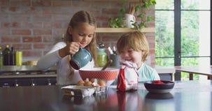 Rodzeństwa przygotowywa ciastko na worktop w kuchni przy wygodnym domem 4k zbiory wideo