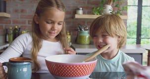Rodzeństwa przygotowywa ciastko na worktop w kuchni przy wygodnym domem 4k zbiory