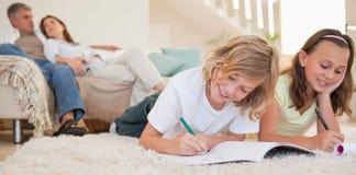 Rodzeństwa robi ich pracie domowej na dywanie zdjęcia royalty free
