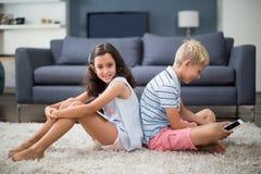 Rodzeństwa siedzi z powrotem popierać podczas gdy chłopiec używa cyfrową pastylkę Obraz Royalty Free