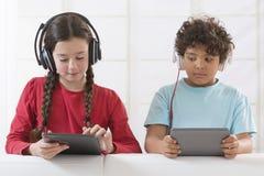 Rodzeństwa używa cyfrową pastylkę podczas gdy słuchający obrazy royalty free