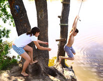 rodzeństwa brat i siostra one zabawiają z wody huśtawką na wakacje Fotografia Stock