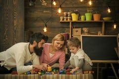 Rodzica chudy naprzód ich dzieciak na kanapie Rodzinna sztuka z budowa blokami Tata patrzeje jego ruchliwie syna zdjęcia royalty free