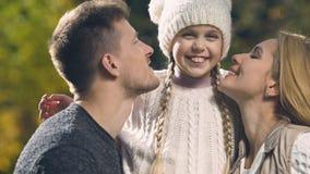 Rodzice całuje szczęśliwej córki na policzkach, wychowaniu i miłości dla dziecka oba, zbiory wideo