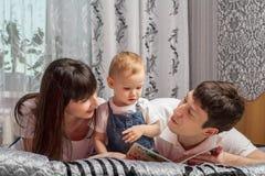 Rodzice czytający książkowego dziecka Zdjęcie Royalty Free