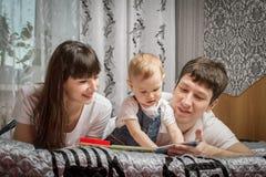 Rodzice czytający książkowego dziecka Zdjęcia Stock