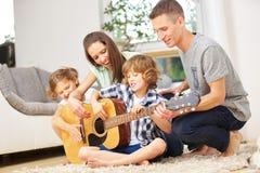 Rodzice i dzieci bawić się gitarę fotografia royalty free