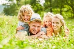 Rodzice i dzieci kłamają szczęśliwie w trawie zdjęcie royalty free