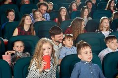 Rodzice i dzieci ogląda film w kinowym i zabawnym zdjęcie royalty free