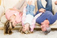 Rodzice i dziecko do góry nogami na leżance Zdjęcia Royalty Free