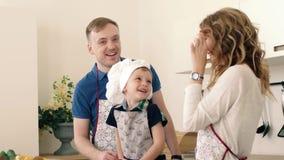 Rodzice i ich syn przygotowywają sałatki warzywa i owoc w kuchni One uśmiechają się przy each sztuką z i innym zbiory wideo
