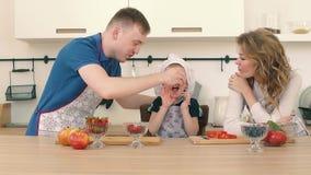 Rodzice karmią ich syna z truskawkami w kuchni Przygotowywają śniadanie zbiory