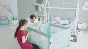 Rodzice ma zabawę z dziecko pozycją w kojec zbiory